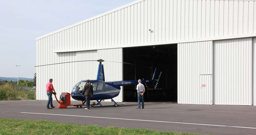 White Aircraft Hangar with large doors built fast with steel structure.